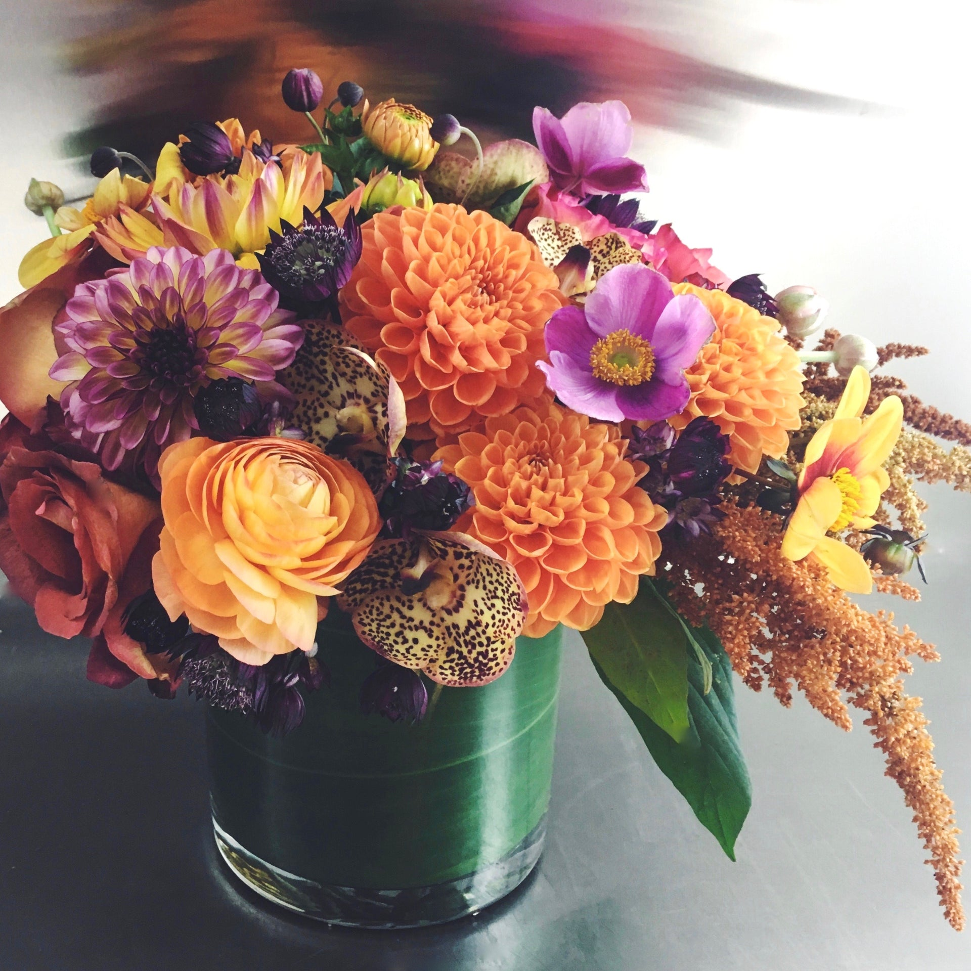 Fall arrangement using dahlias, ranunculus, and amaranthus in a low glass vase.