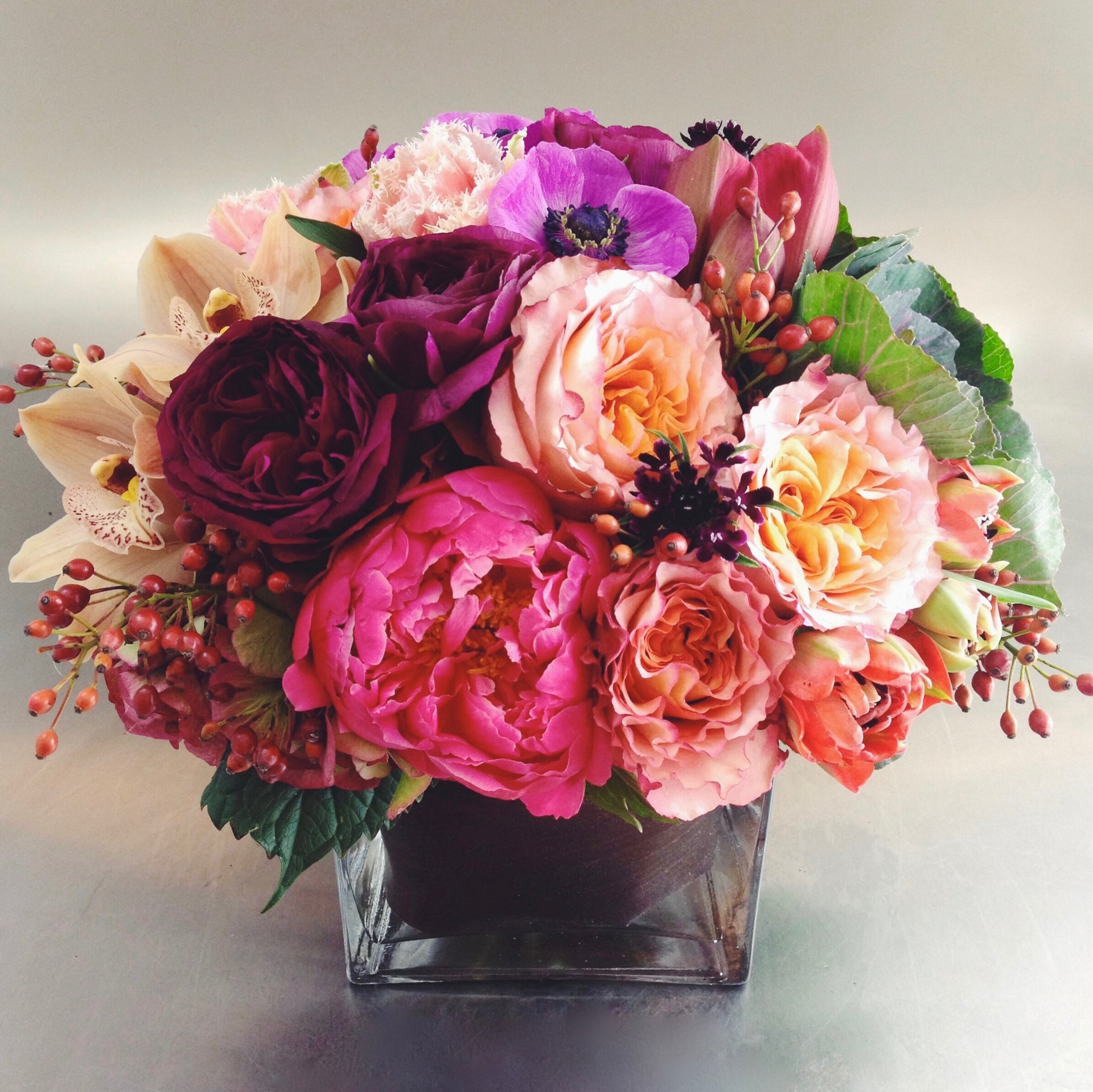 Fall arrangement using roses, kale, and berries available for delivery.