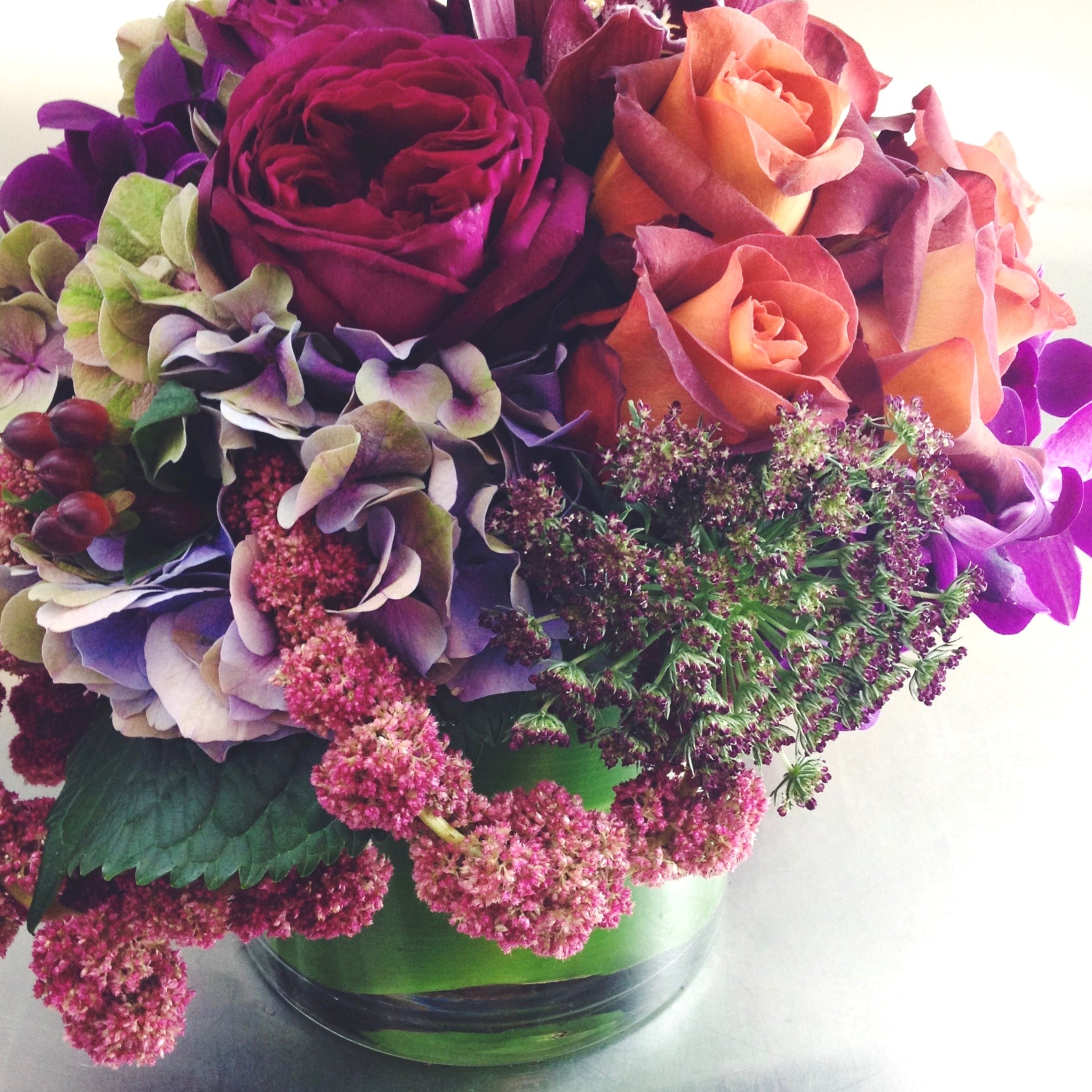 Fall arrangement using roses, berries, and amaranthus in a low glass vase.