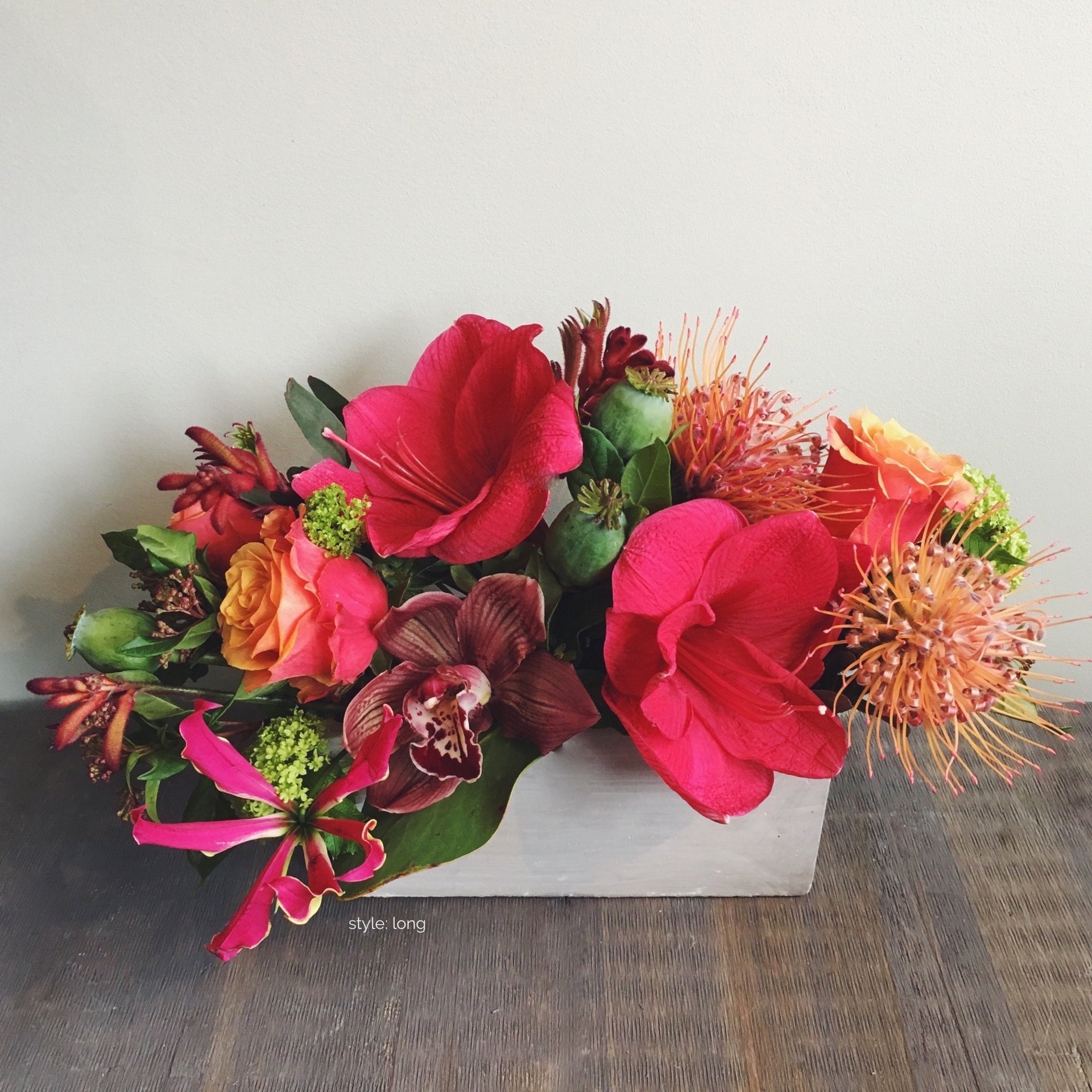 Long bold and bright arrangements using amaryllis, protea, and roses.