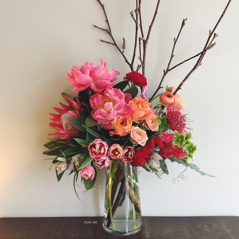 Tall colorful arrangement using peony, protea, and tulips.