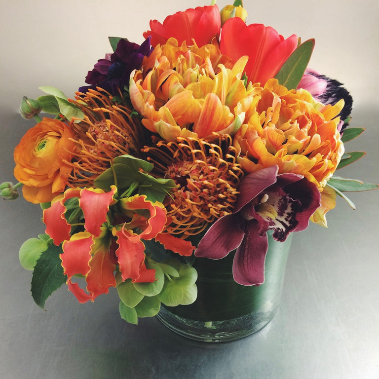 Bold and bright low arrangement using tulips, gloriosa, and ranunculus.
