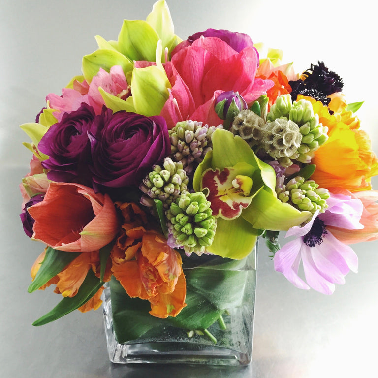 Bold and bright low arrangement using hyacinth, orchids, and tulips.