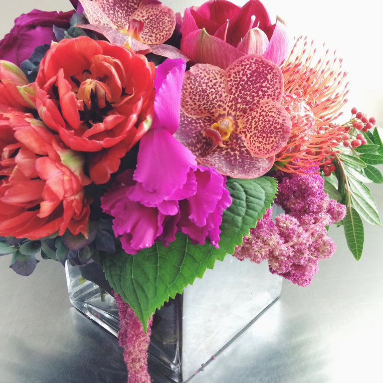Bold and bright low arrangement using tulips, vanda orchids, and anemones.