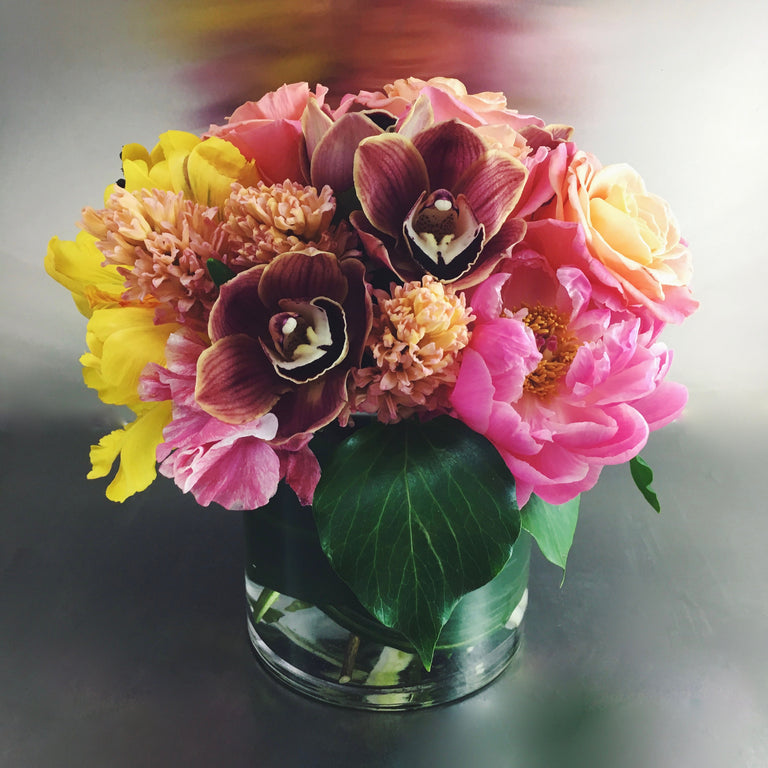 Colorful low arrangement using peony, orchids, and protea.