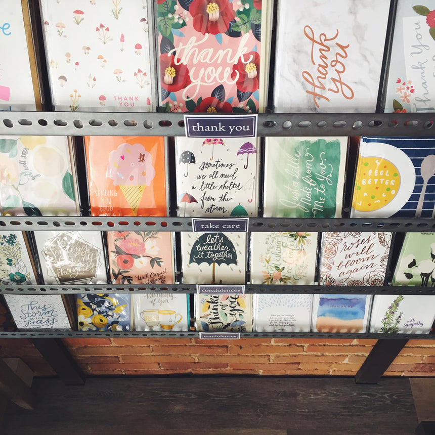 Greeting cards by independent designers displayed on card racks at cymbidium floral.
