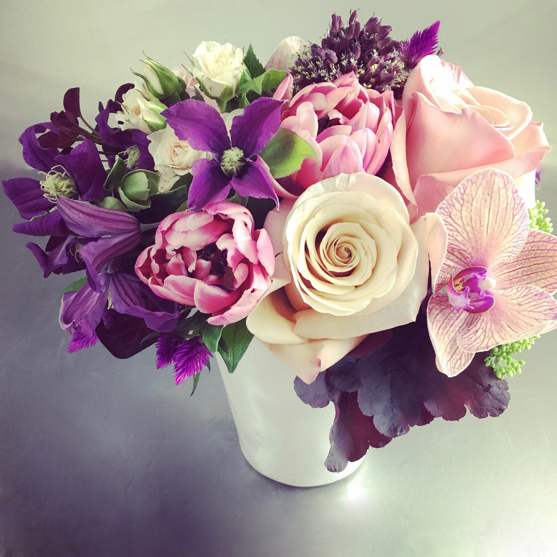 Designer's choice low arrangement using orchids, tulips, and roses.