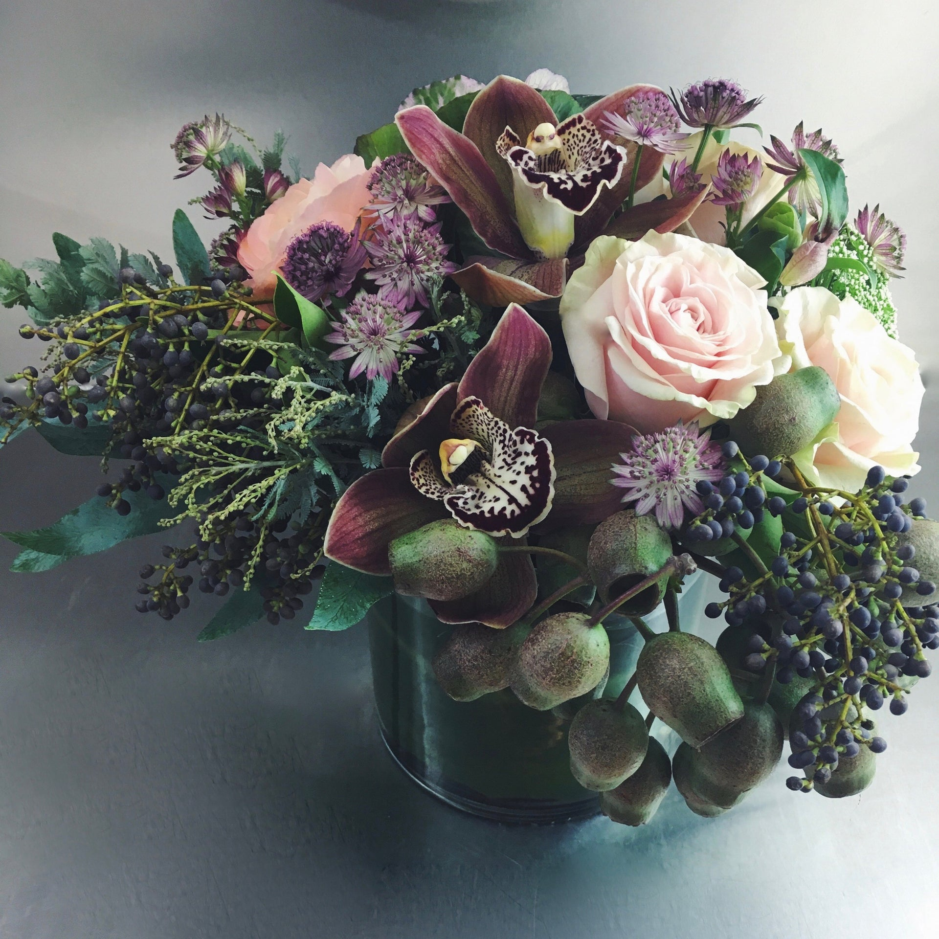 Designer's choice low arrangement using orchids, roses, and privet berries.