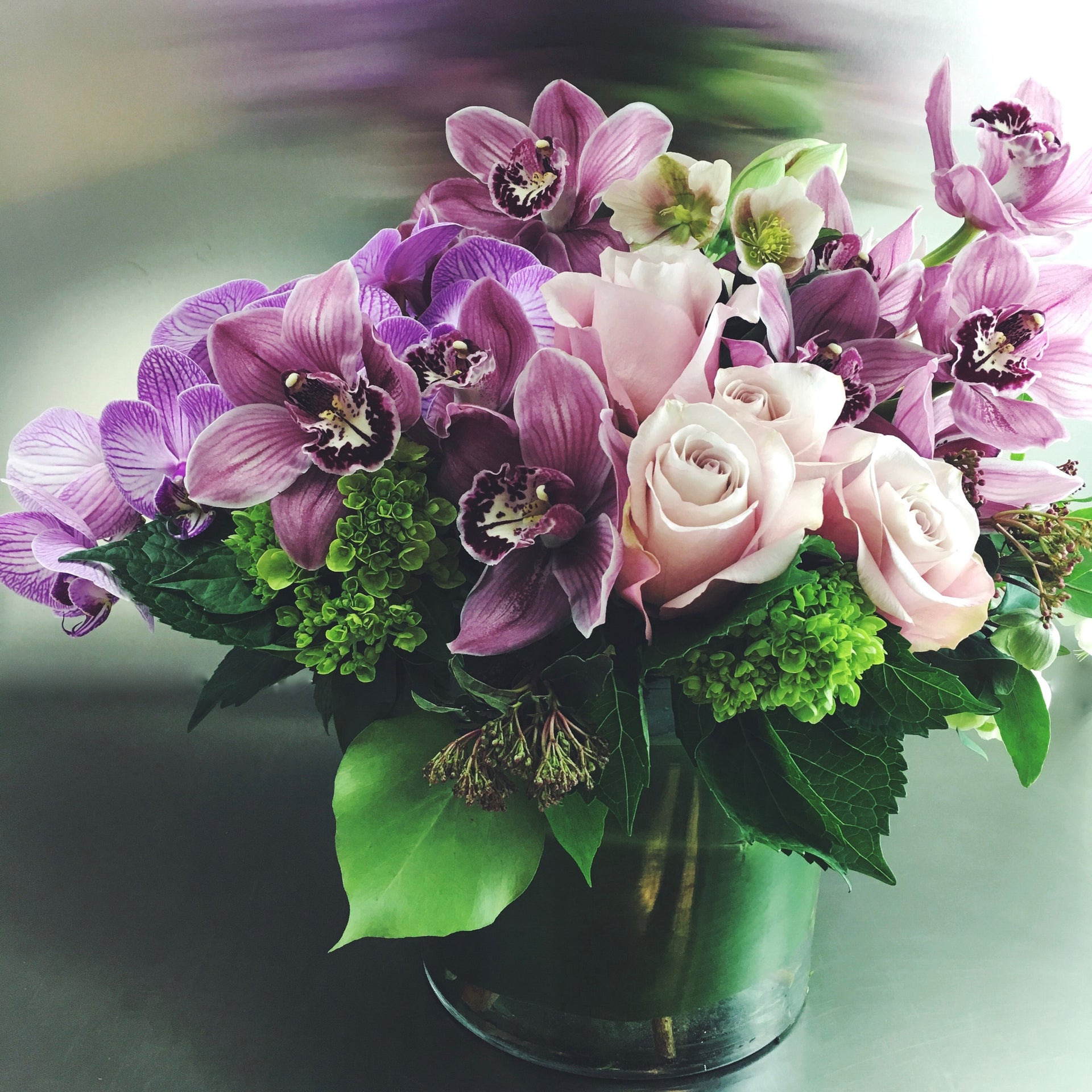 Designer's choice low arrangement using cymbidium orchids, roses, and hydrangea.