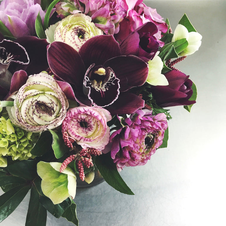Designer's choice low arrangement using cymbidium orchids, ranunculus, and hydrangea.