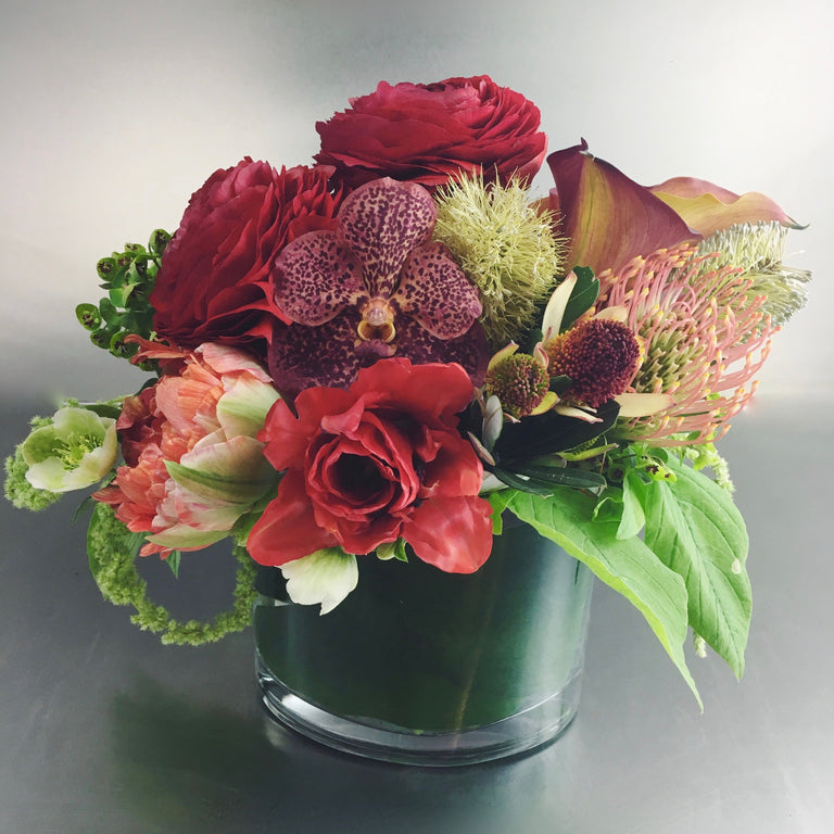Designer's choice low arrangement using orchids, tulips, and calla lilies.