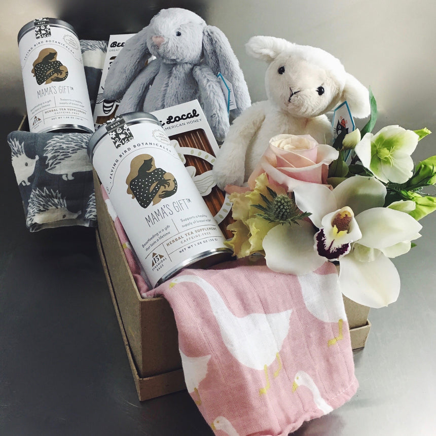 Gift box for baby and mom including stuffed animal, flowers, tea, honey, and burp cloth.