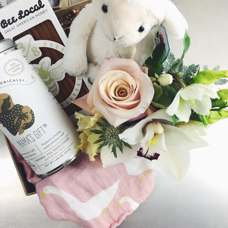 Gift box for baby and mom including bunny stuffed animal, flowers, tea, honey, and burp cloth.