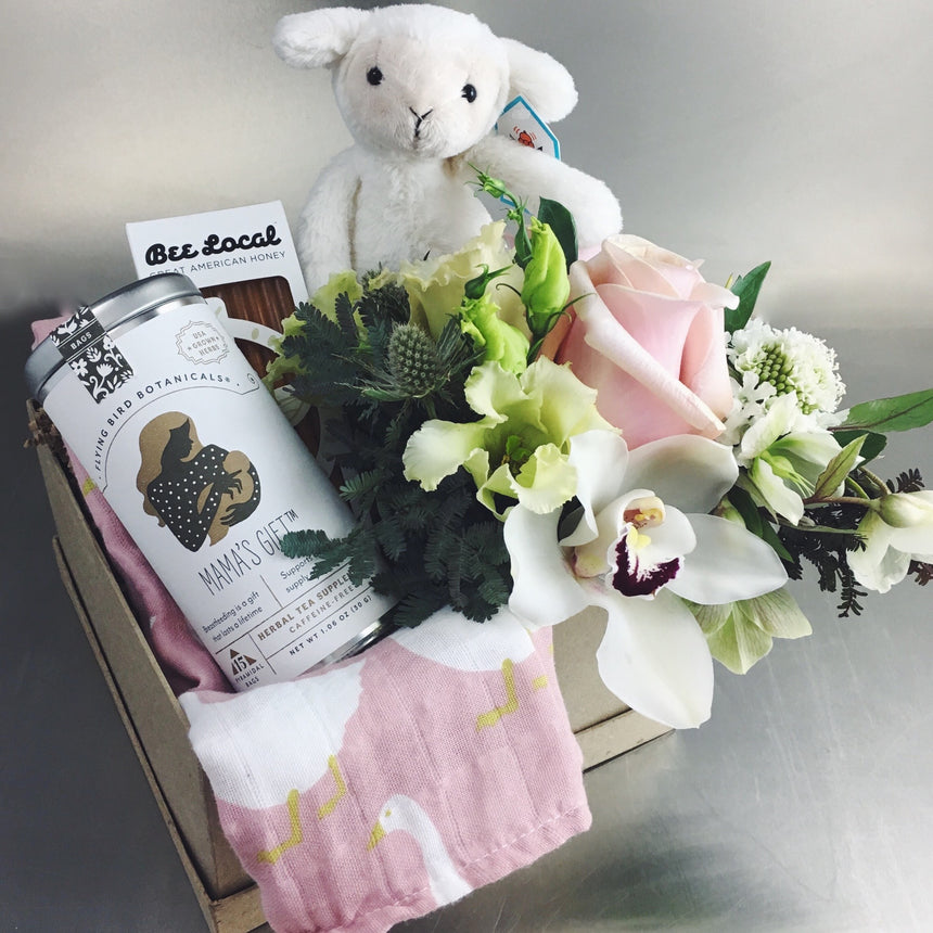 Gift box for baby and mom including lamb stuffed animal, flowers, tea, honey, and burp cloth available for delivery.
