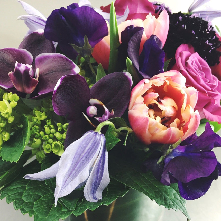 Rich and romantic low arrangement with tulips, clematis, and orchids.
