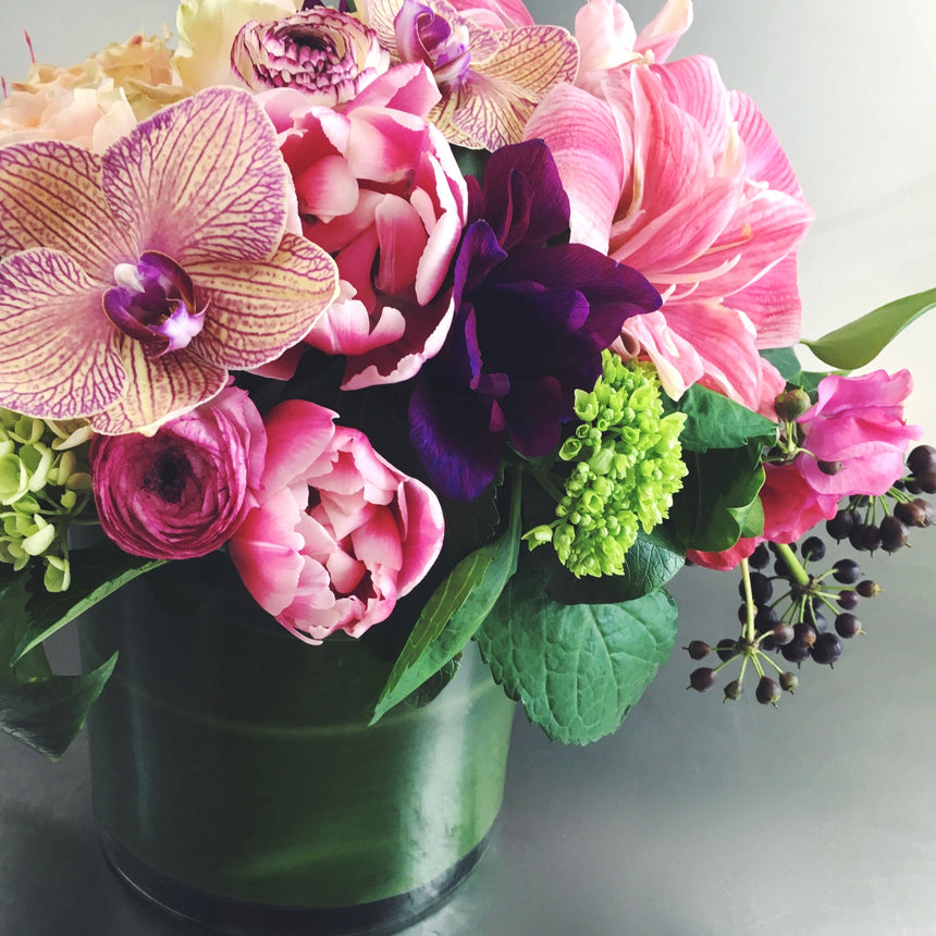 Rich and romantic low arrangement with orchids, ranunculus, and anemones.