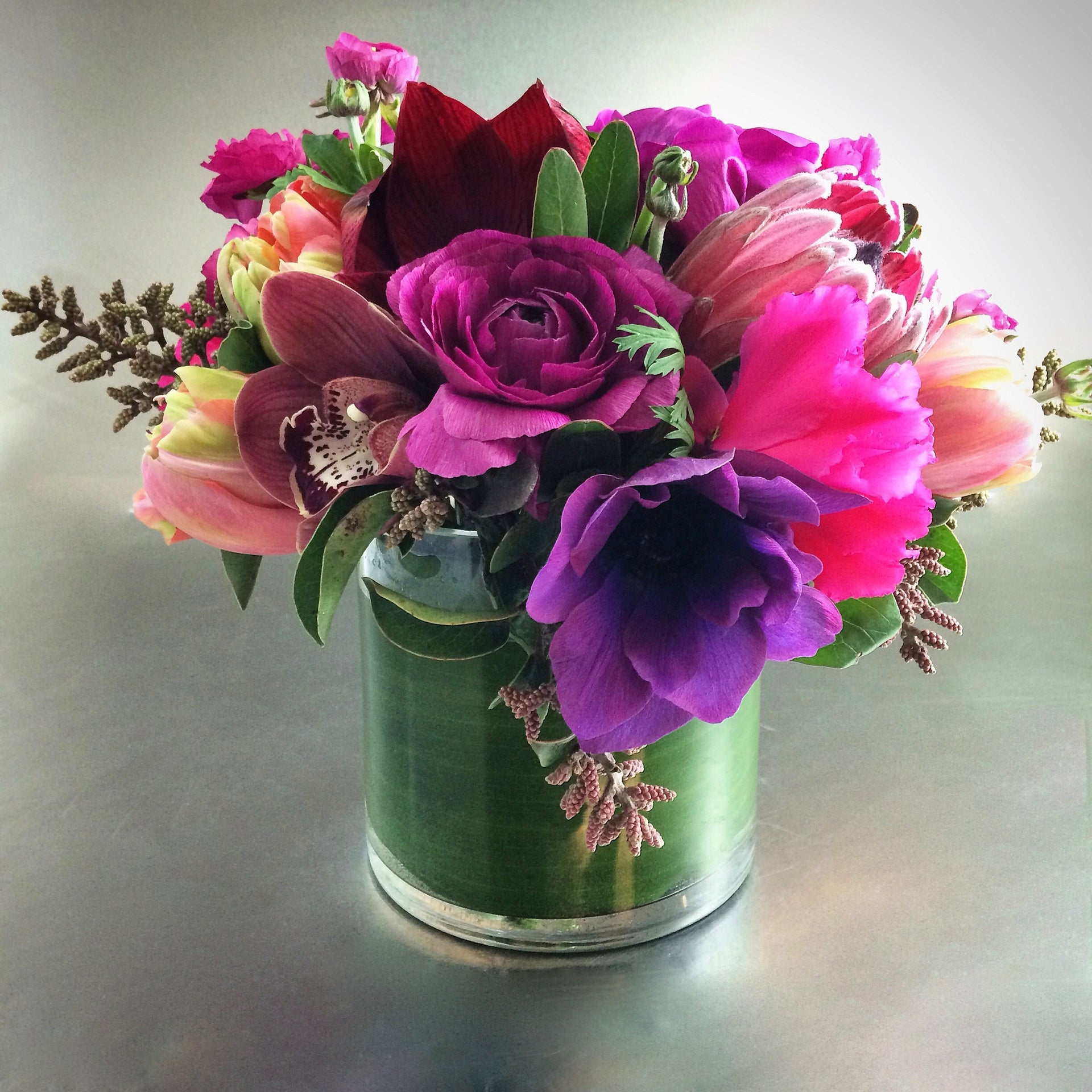 Rich and romantic low arrangement with anemones, roses, and ranunculus.