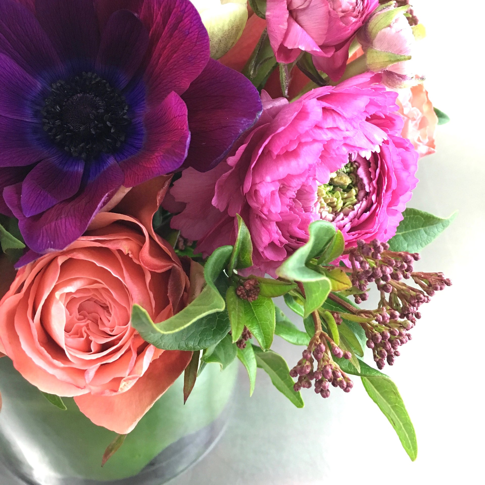Arrangement with rose, anemone, and ranunculus.