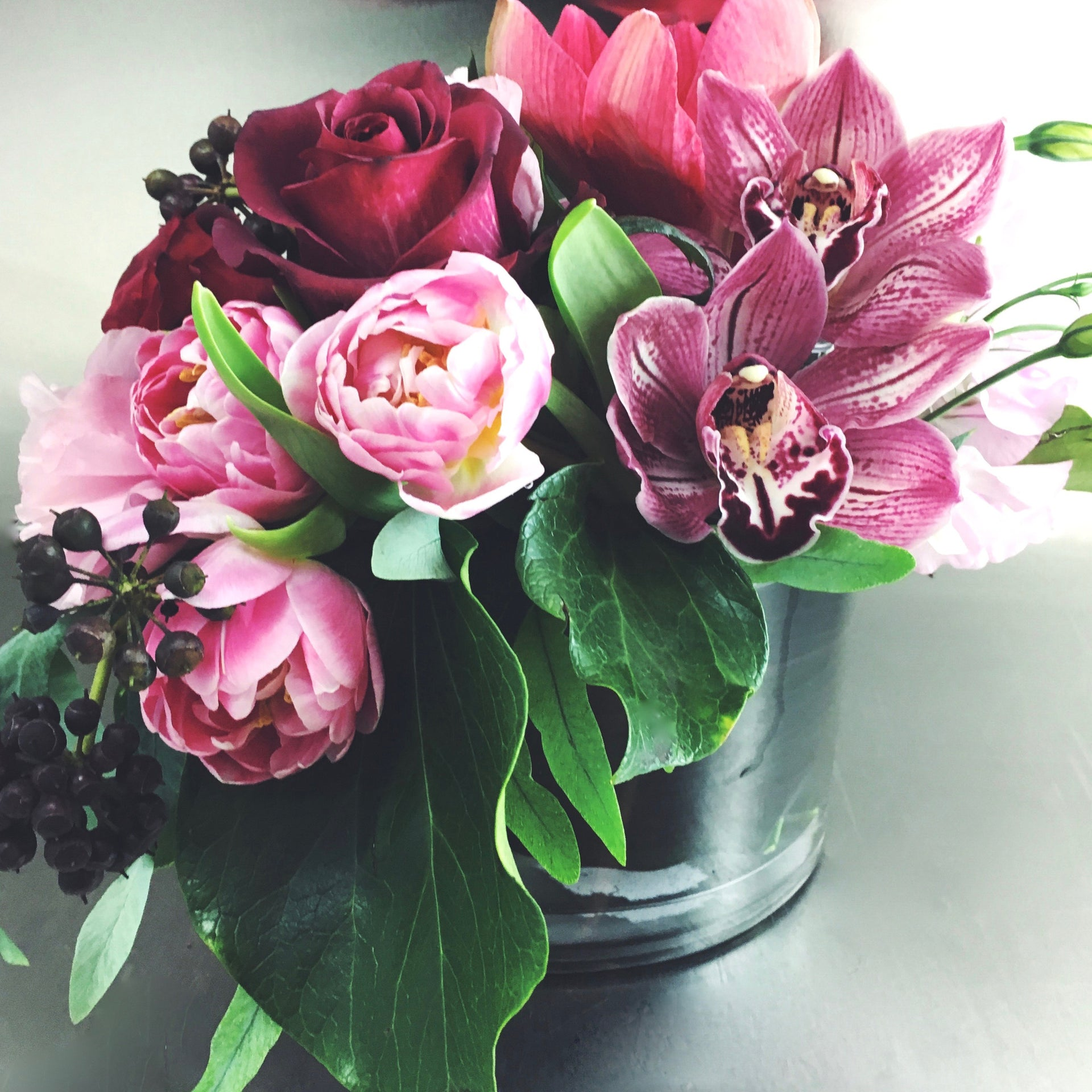 Rich and romantic signature low arrangement with tulips, cymbidium orchids, and roses, available for delivery.