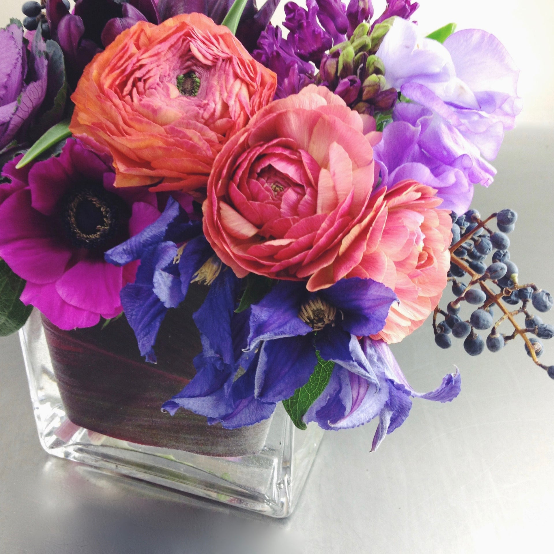 Rich and romantic low arrangement with anemones, ranunculus, and clematis.