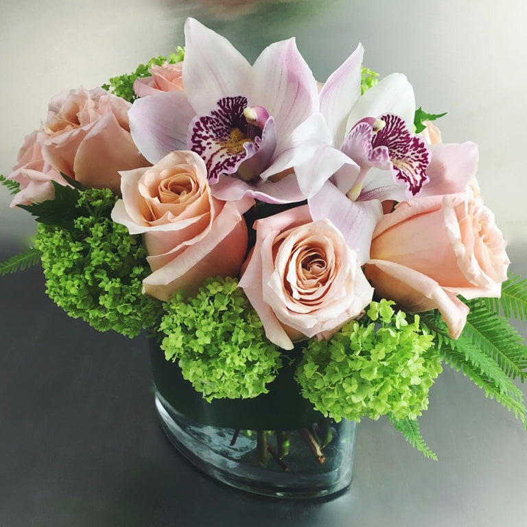 Dozen roses with cymbidium orchids available for delivery.