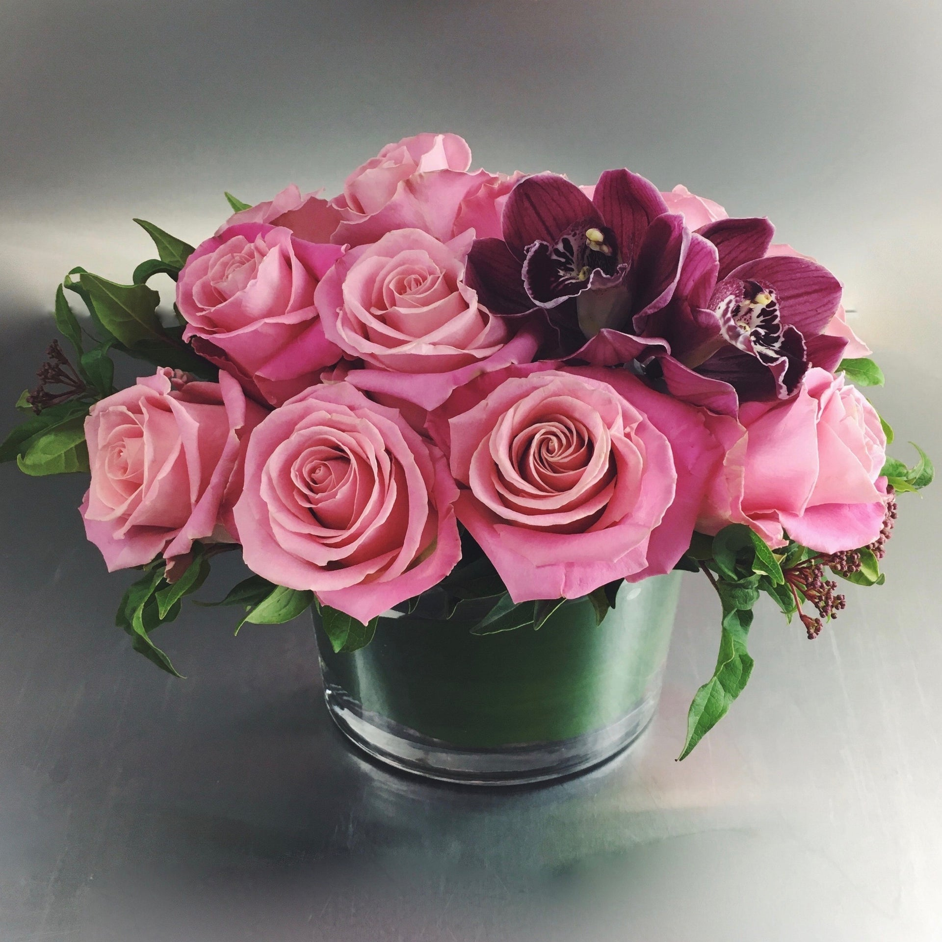 Dozen pink roses with cymbidium orchids in a low vase.
