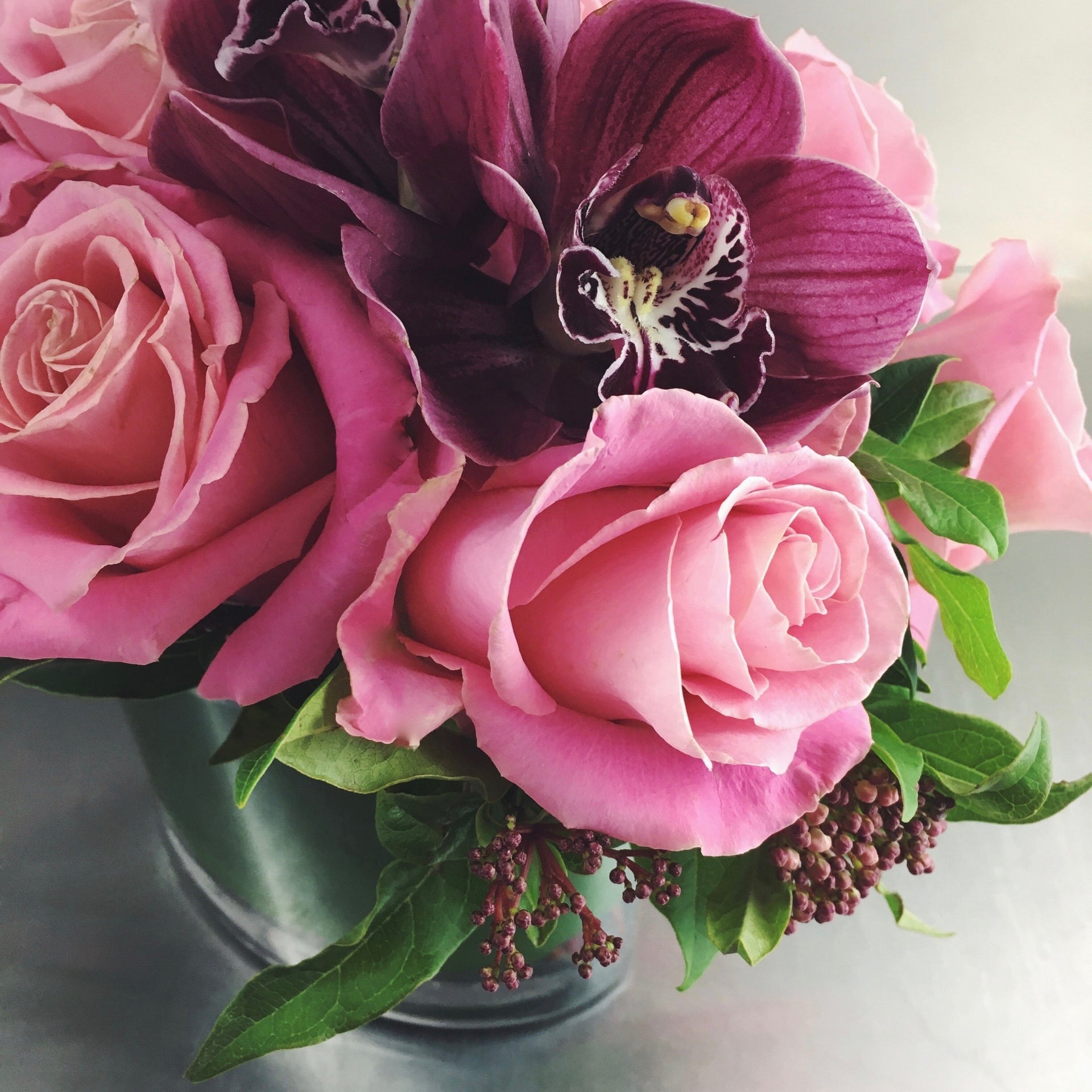 Pink roses and burgundy cymbidium orchid.