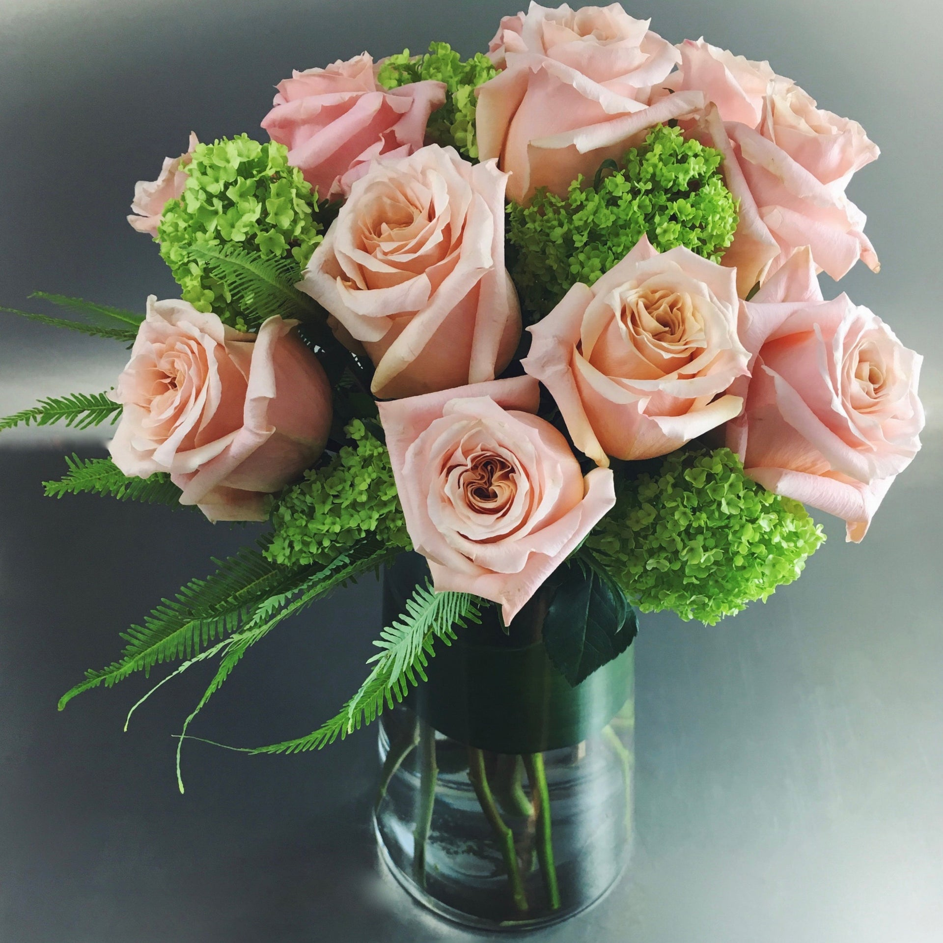 Long stemmed dozen roses accented by greenery in a vase.