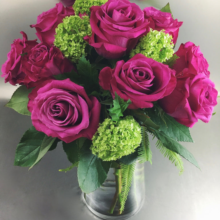 Dozen hot pink roses and greenery in a tall glass vase.