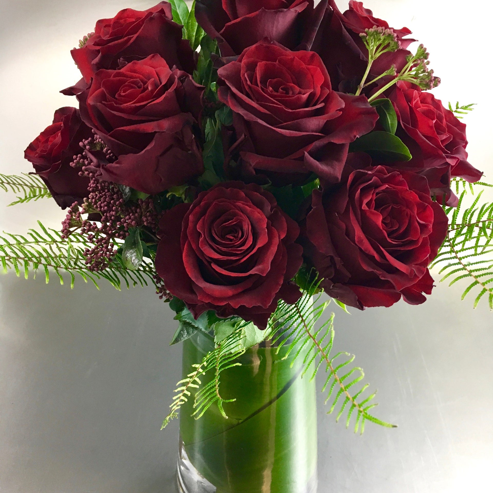 Dozen red roses and greenery in a tall glass vase.