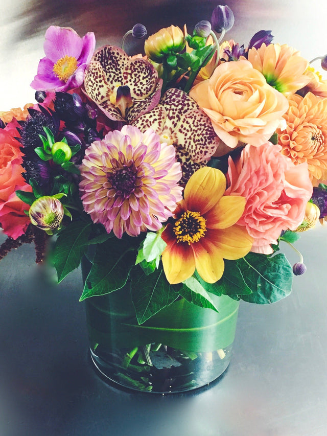 Fall arrangement using dahlias, roses, and orchids in a low glass vase.
