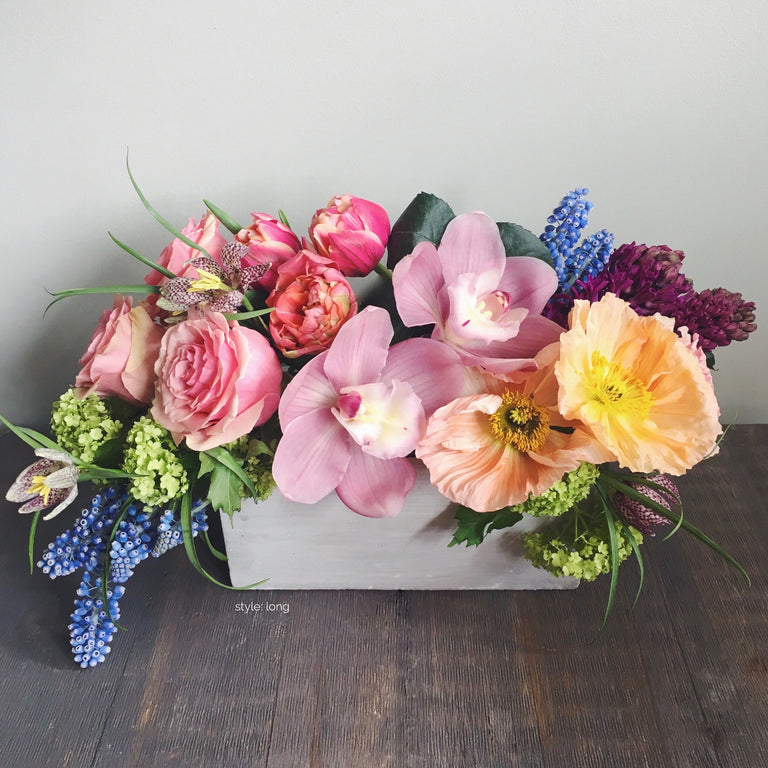 Designer's choice long arrangement using poppies, muscari, and ranunculus.