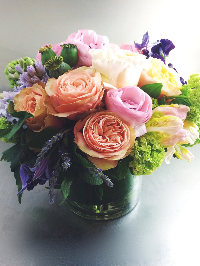 Spring arrangement using roses, tulips, and hyacinth in a low glass vase.