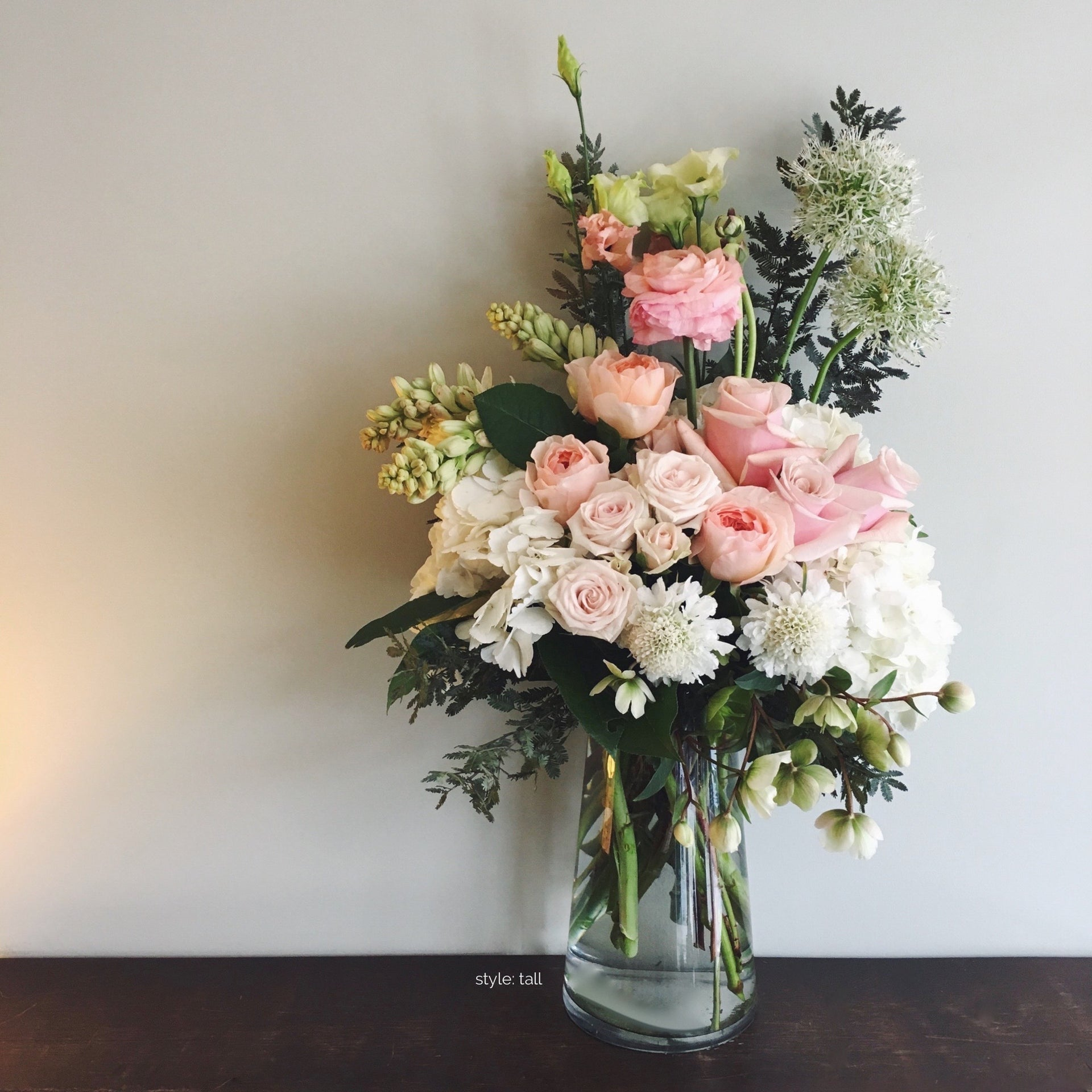 Tall soft and subdued arrangement in white, light pink and green using roses, hydrangea, and allium.