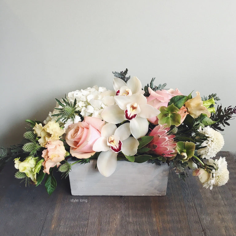 Long soft and subdued arrangement in white, pale pink, and cream with orchids, roses, and tulips.