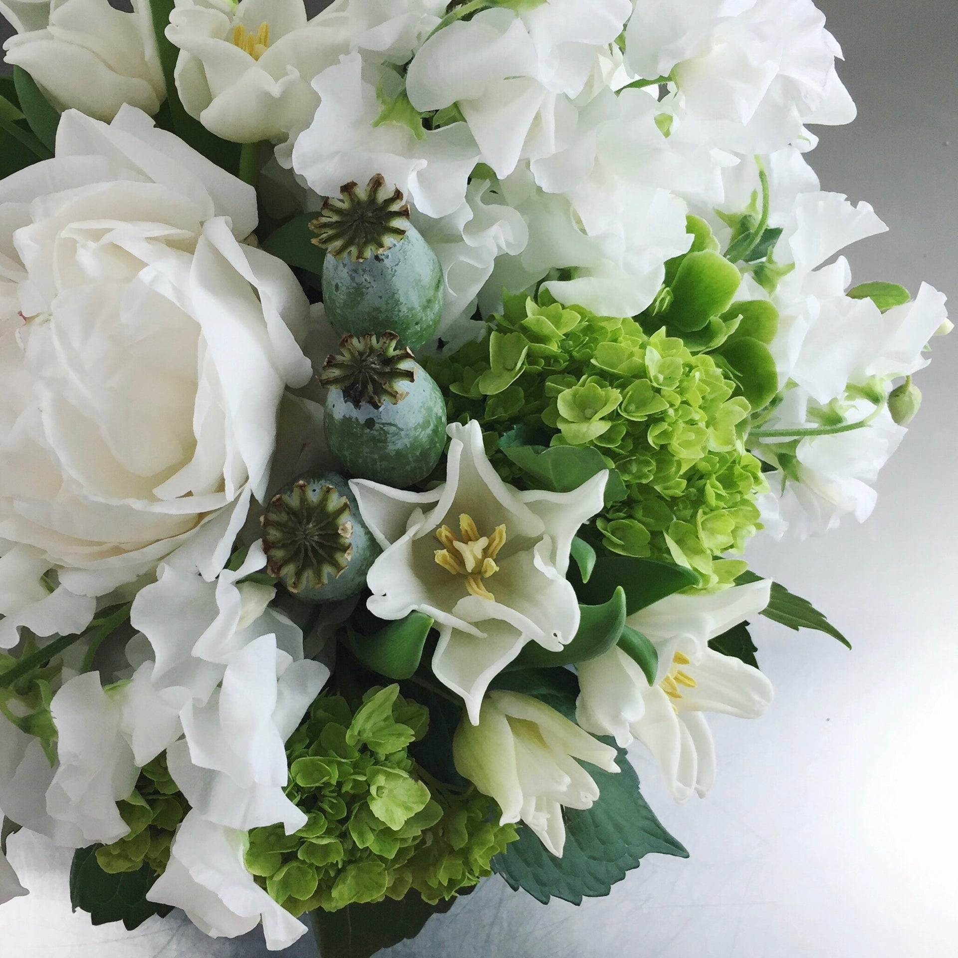 White and green arrangement of peonies, poppy pods, and sweetpea.