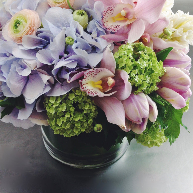 Soft and subdued arrangement in lavender, pale pink, and green using hydrangea, orchids, and viburnum.