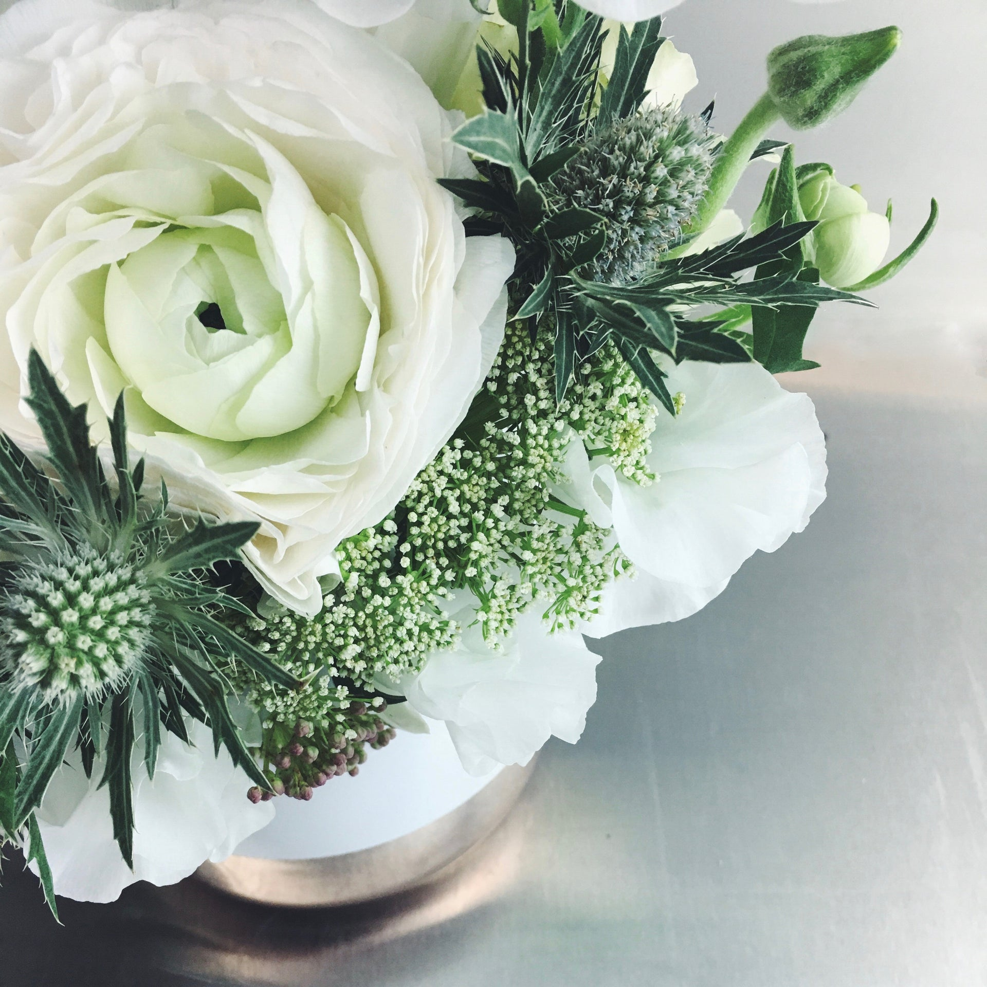Soft and subdued arrangement in white and green with ranunculus and thistle.