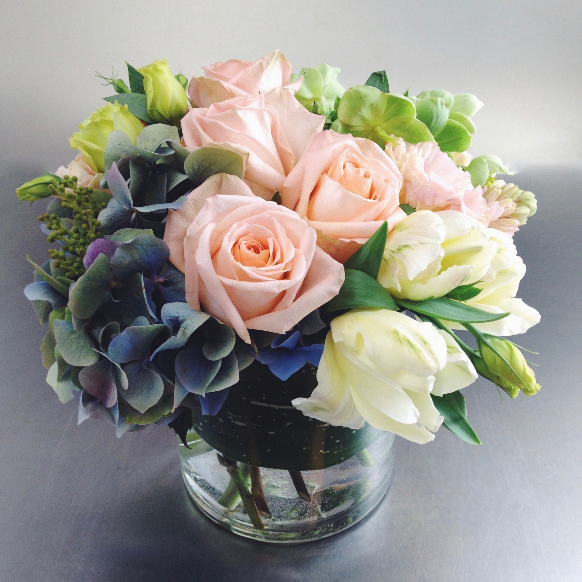 Soft and subdued arrangement in blue, peach, and cream with hydrangea, roses, and tulips.