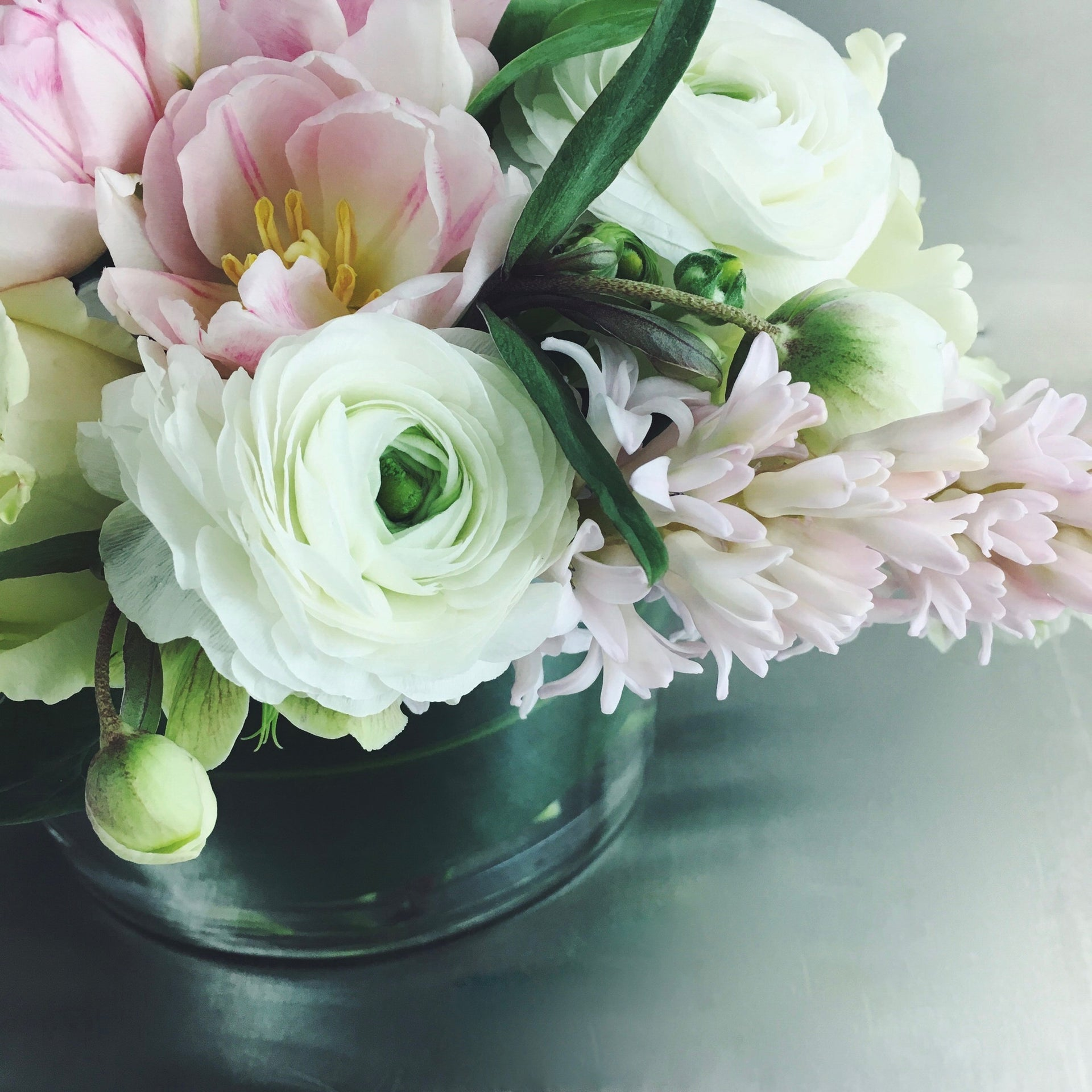 Soft and subdued arrangement in white and pale pink using hyacinth, tulips, and ranunculus.