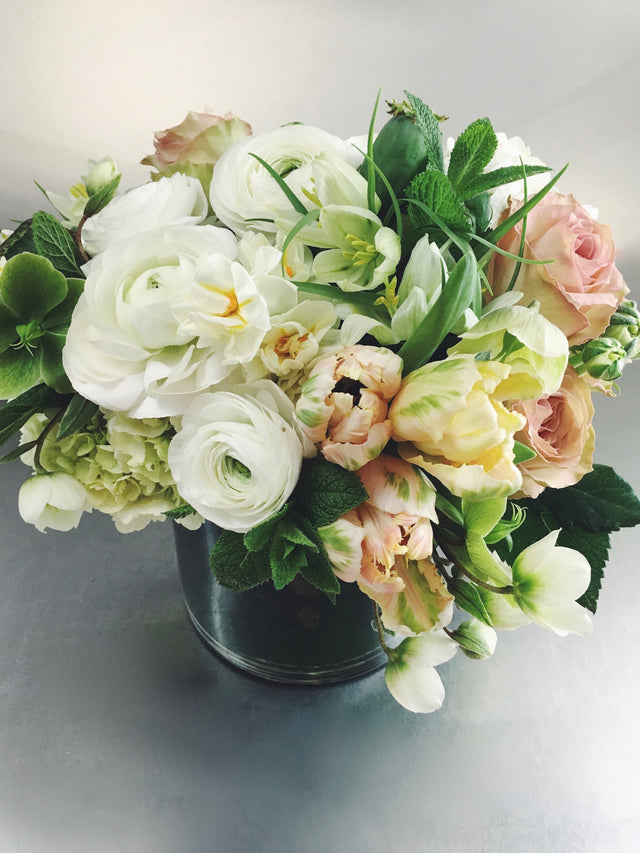 Soft and subdued arrangement in white, peach and green with tulips and ranunculus.