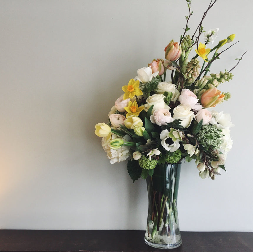 Tall sympathy arrangement in white and yellow perfect for the funeral service or home.