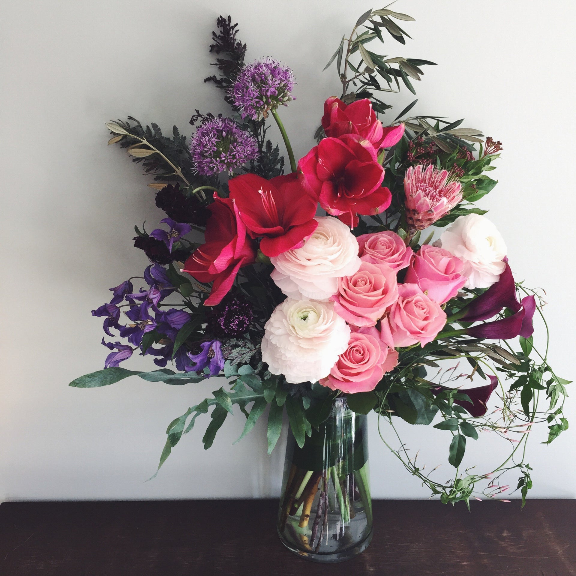 Large arrangement in bright pink, purple, light pink to express your condolences.