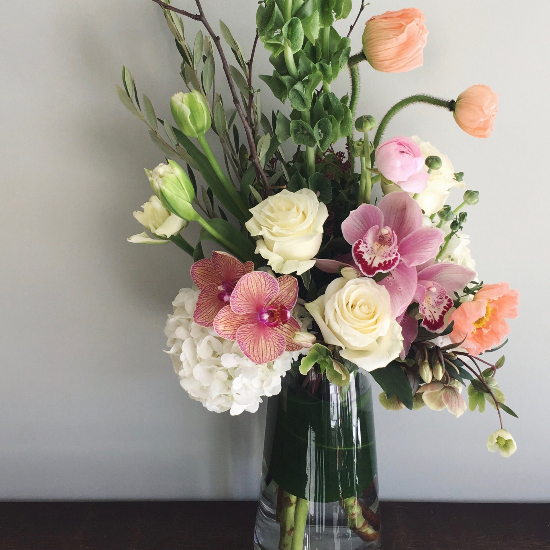Large arrangement of flowers in white, peach, and pink in a glass vase.