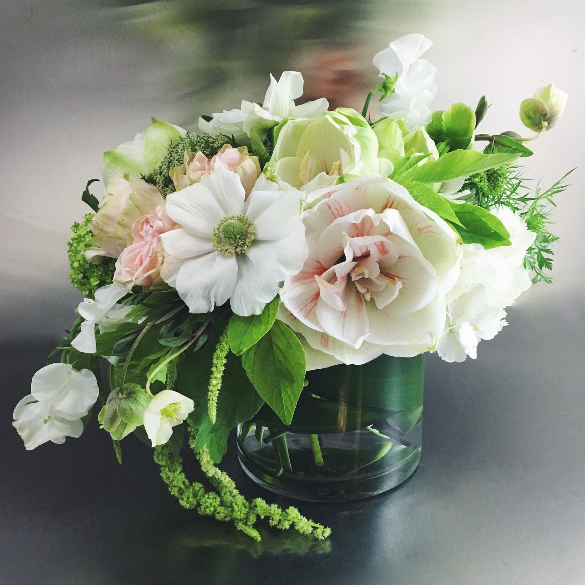 Low arrangement in white, pale pink and green to express your condolences.