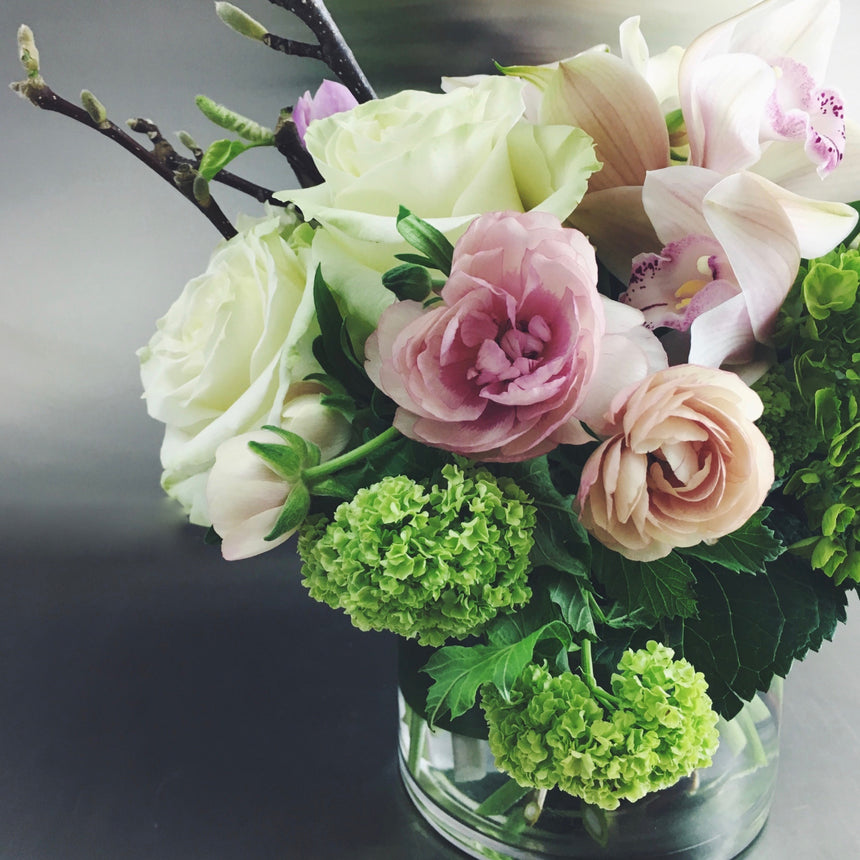 Sympathy arrangement with ranunculus and roses in glass vase.