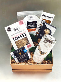 Gift box with nuts, toffee, peanut butter cup, chocolate bar, tea, and honey sticks.