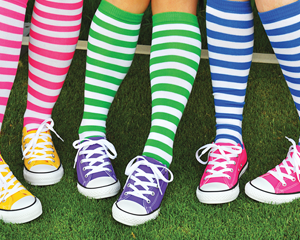 Brightly colored converse shoes and Everything Sport socks with grass background