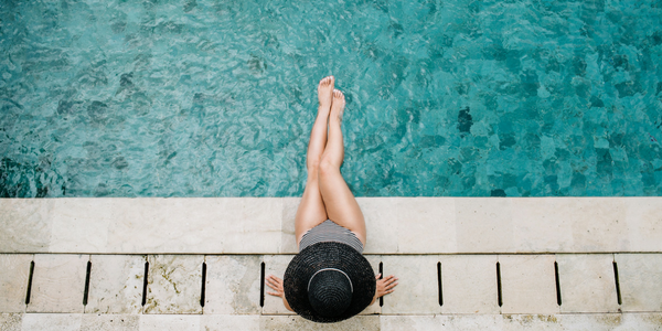 Woman sitting at blue swimming pool