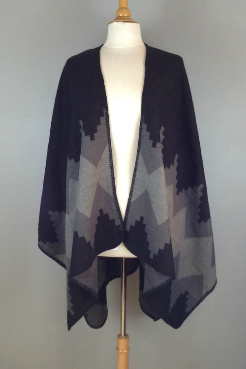 black and grey reversible poncho wrap features bold graphic print and blanket stitch detail.